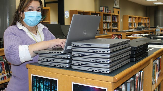 Blackstone Valley Regional Vocational Technical High School Technology Director Rosetta Spino prepares Dell laptops for distribution.