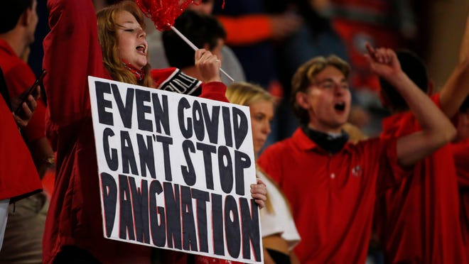 Georgia fans root on their team against Auburn on Oct. 3. Georgia requires all fans to wear a mask when they enter the stadium and move around inside it  but not while at their assigned seats.