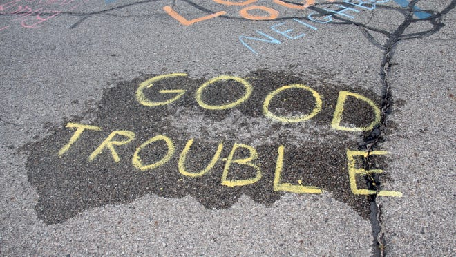 """The phrase """"good trouble"""" is written in chalk. The phrase was coined by the late-civil rights icon John Lewis."""