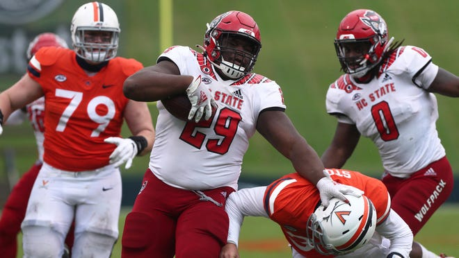 NC State nose tackle Alim McNeill (29) takes an interception back for a touchdown against Virginia on Oct. 10. McNeill was named second-team All-American this week and will play for the Wolfpack in the TaxSlayer Gator Bowl on Sunday.