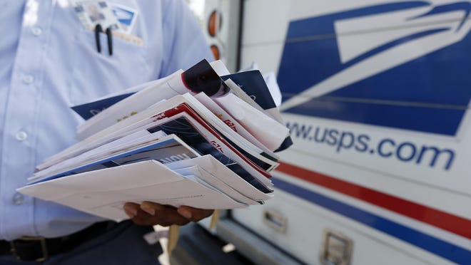 FILE - In this Aug. 7, 2014, file photo, a U.S. Postal Service letter carrier prepares to deliver mail on his route in the 8200 block of Green Hollow Lane in Dallas.