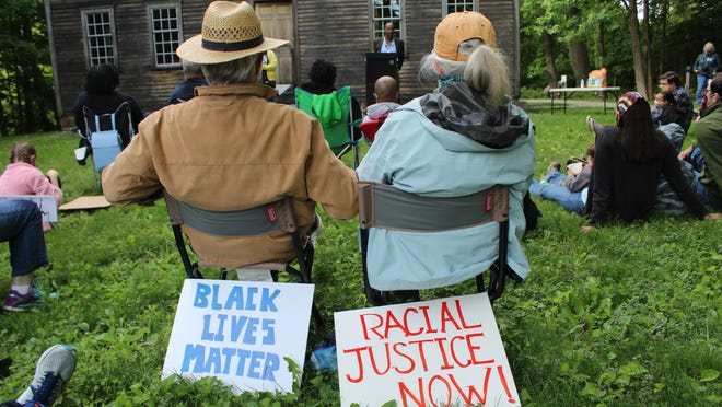 Attendees at the protest at the Robbins House display signs against racial injustice on June 1.
