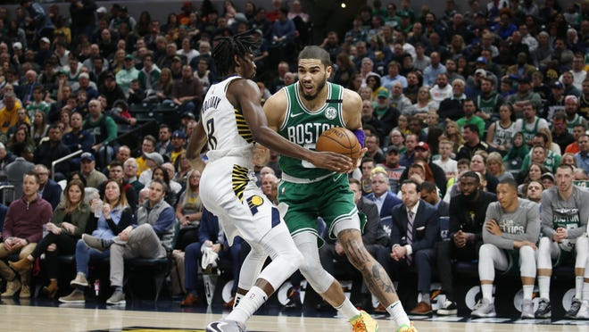 Boston Celtics forward Jayson Tatum (0) drives to the basket against Indiana Pacers guard Justin Holiday (8) during the fourth quarter at Bankers Life Fieldhouse on March 10, 2020..