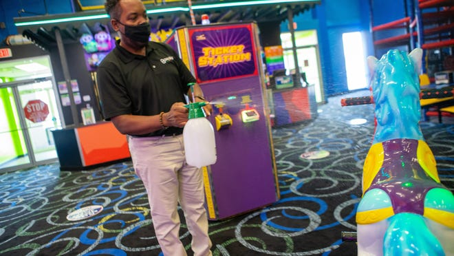 Terance Lard, Bonkers' regional director of operations, shows how the business uses a sanitizing spray to disinfect play equipment Thursday at Bonkers' Topeka location, 5515 S.W. 21st St.