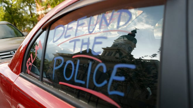 City Hall is reflected in the window of a car during a demonstration in Athens, Ga., on Wednesday, July 1, 2020.