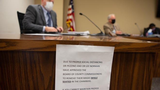 A sign is taped to the table where Shawnee County commissioners conduct business at an August commission meeting to inform those in attendance about proper social distancing measures.
