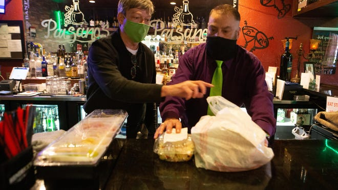 Paisano's Ristorante owner Steve Butland, left, helps Doug Pollock, a Paisano's bartender, with to-go orders  at the restaurant's Topeka location, 4043 S.W. 10th Ave. [2020 file photo/The Capital-Journal]