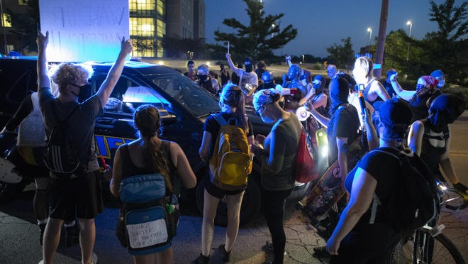 Protesters surround a Winnebago County Sheriff's Office squad car on West State Street on Saturday, July 4, 2020, in Rockford.