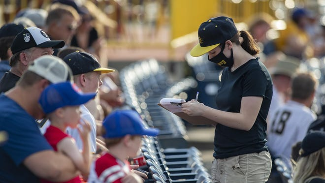 A Rockford Rivets worker takes orders during the game on Wednesday, July 1, 2020, at Rivets Stadium in Loves Park. It is believed to be the first sporting event played in front of paid spectators in Illinois since the COVID-19 pandemic shut down the state.