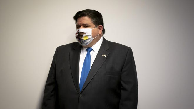 """Illinois Governor JB Pritzker listens as IEMA Director Alicia Tate-Nadeau introduces him to unveil a new mask awareness campaign called """"It Only Works If You Wear It"""" during a press conference at the IEMA State Emergency Operations Center, Monday, August 3, 2020, in Springfield."""
