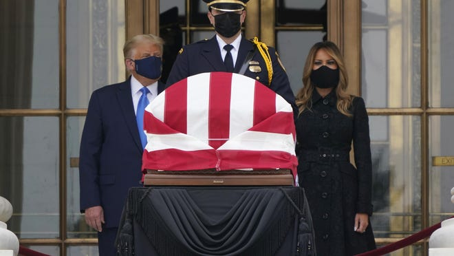 President Donald Trump turns to his left as protesters yell from a block away while he and first lady Melania Trump pay respects as Justice Ruth Bader Ginsburg lies in repose at the Supreme Court building on Thursday, Sept. 24, 2020, in Washington. Ginsburg, 87, died of cancer on Sept. 18.