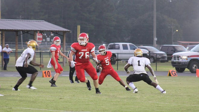 Bryan County High School freshman running back Jacari Carney (5) looks to hit the hole behind blocking of Chanler Moore (76) during a game earlier this season.