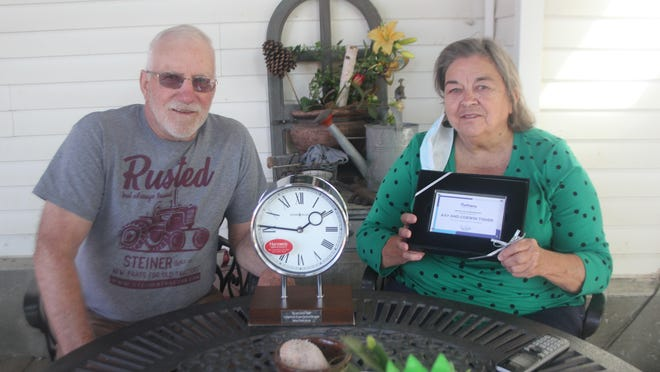 Corwin (left) and Kay Tischer pose with a clock and placque commemorating their 56 years as foster parents on Thursday, Sept. 17, at their home in Lake Odessa.