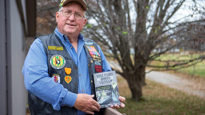 "Stephen R. Williams holds up his recently published book, ""Nine Pairs of Boots in Vietnam: Steps to Healing Every Veteran Needs to Know,"" while standing on his patio Monday afternoon. Williams and his wife, Rosie, released their book to be available on Veterans Day."