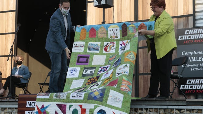 Caleb Asher, left, and Kathy Pflaum, right, hold up a quilt that Pflaum helped create to commemorate the NOTO Arts & Entertainment District's tenth anniversary. [2020 file photo/The Capital-Journal]