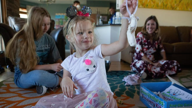 Liza Eckert, 4, creates a bracelet from items in the Snow-Ventures Discovery Kit from the Kansas Children's Discovery Center while her older sister Kate Eckert, 14, left, and mom, Christie Applehanz, right, also enjoy items from the boxes at their home Wednesday afternoon.