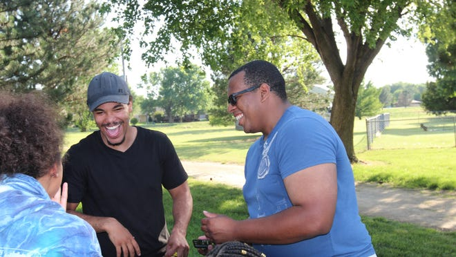Demei Jobe, left, and Officer Airen Maxwell laugh about their team's solution to a Godzilla-themed problem solving game at Friday's Bridgebuilders BBQ event.