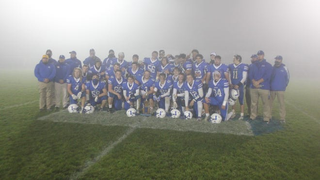 The Ionia varsity football team poses with a trophy after defeating rival Lake Odessa Lakewood 42-7 Thursday, Oct. 22, at Lloyd T. Smith Memorial Field. Ionia heads into the playoffs with a 1-5 record.