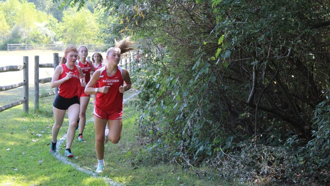 Runners come around a turn during Saturday's girls cross country dual meet between Bedford and Monroe in Temperance.