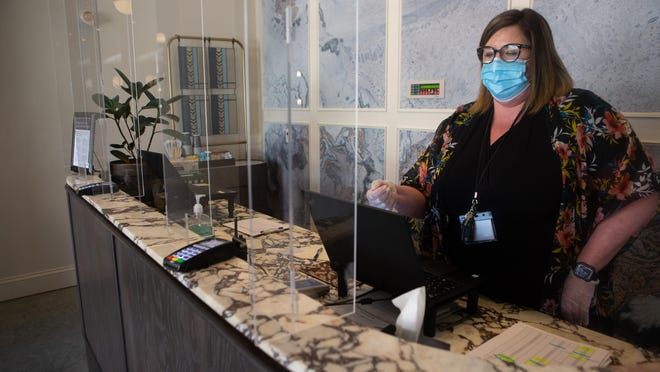 The Cyrus Hotel's general manager Colleen Lynch talks Tuesday afternoon about the various steps hotel staff have taken to reopen the boutique hotel to guests. Plexiglass has been placed around the reception area, distance markers and hand sanitizer are available throughout the hotel and housekeeping personnel are taking extra precautions while cleaning.