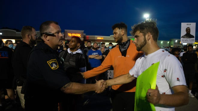 Topeka police Lt. Steve Roth shakes hands with protesters Tuesday during a demonstration at West Ridge Plaza near S.W. 21st and Wanamaker in the wake of protests started after the death of George Floyd at the hands of a Minneapolis police officer.