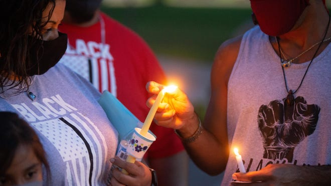David Matthew Rodriguez, right, helps light candles during a vigil event Thursday at the south steps of the Capitol for the event 'Say Their Names - In remembrance of all lives lost.'
