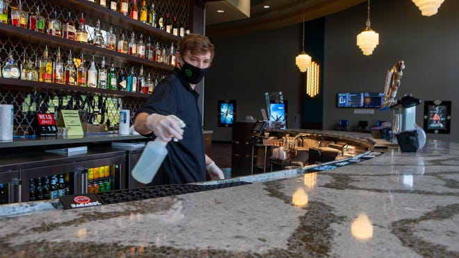 Michael Sallman, an employee at B&B Theatres, uses a sanitizing spray to wipe down the bar counter inside the theater Friday afternoon.