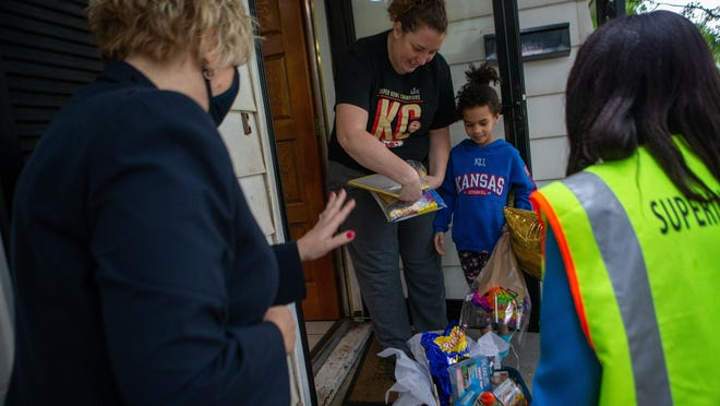 Kindergartner Kassidy Vandyke receives a welcome Wednesday morning for her first day of school as Tiffany Anderson, right, USD 501 superintendent, and Sue Bolley, Topeka Board of Education member, surprises her and her mom, Pam Vandyke, Wednesday morning by supplying them with school supplies.