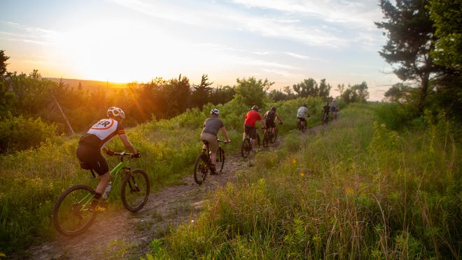 Cyclists ride a portion of the Sunset Loop of Azura Trails at Skyline Park last month. The trail system incorporates a mix of terrain from rocky sections and wooded areas to prairie fields.