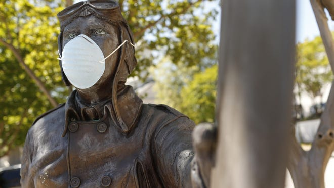 A face mask on the Ben T. Epps statue in downtown Athens, Ga, on Friday, May 1, 2020. Athens-Clarke officials are set to consider a mask-wearing mandate.