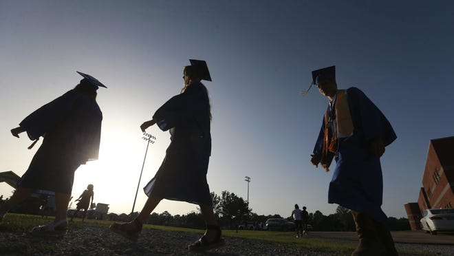 Saltillo High School seniors make their way to the football field Saturday, June, 27, 2020, as the sun begins to set for their graduation ceremony in Saltillo, Mississippi.