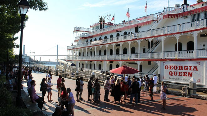 People line up to board a boat for a cruise on the Savannah River on Saturday evening during the Fourth of July holiday.