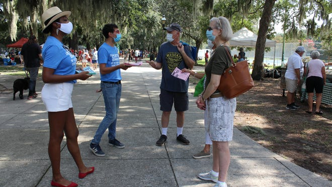 Clinton Edminster (center left), Democratic candidate in the Chatham County Commission's District 2 runoff, greets locals at Forsyth Park on Aug. 8.