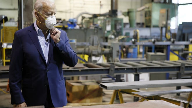 Democratic presidential candidate Joe Biden adjusts his mask during a tour of McGregor Industries, a metal fabricating facility in Dunmore, Pa.