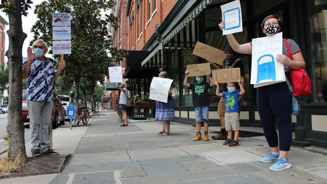 Demonstrators gather outside of Savannah's post office by Telfair Square on Aug. 22 to protest recent actions by Postmaster General Louis DeJoy.