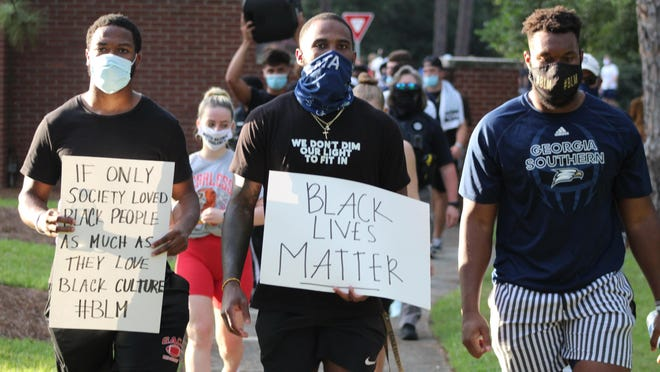 From left to right: Georgia Southern football players Justin Harris, Shai Werts and Rashad Byrd lead the March For Change on Thursday evening on the campus at Georgia Southern University in Statesboro.