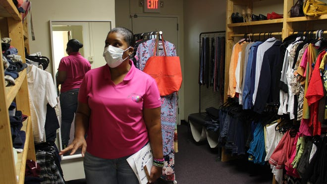 The Front Porch Interim Director Brenda Davis in the facility's fitting room of free high-quality clothing.