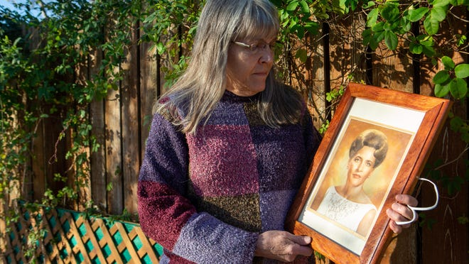 Aleah Mahan holds a portrait of her mother, Anna Roediger, outside her home near Paxico on Friday. Mahan's mother died in early September, weeks after testing positive for COVID-19.