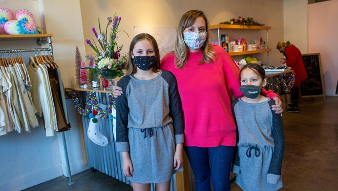 Ashley Dassinger Carson, owner of Lilly Grace, stands with her daughters, and store namesakes, Lilly, left, age 11, and Grace, right, age 8, on Saturday morning at the new boutique, located at 3123 S.W. Huntoon St. in the Westboro Mart shopping center.