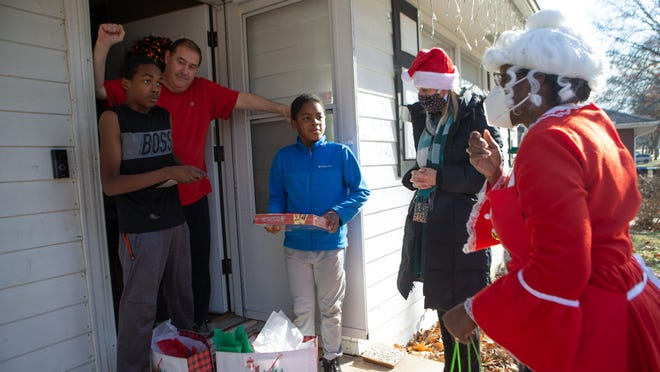 Dressed as Mrs. Claus, USD 501 superintendent Tiffany Anderson accompanies Keelin Pierce, Whitson Elementary principal, in delivering gifts to Richard Sigle, Topeka fire chief for emergency medical services, and his sons Jayden, left, and Kashaun, right, Wednesday afternoon. Anderson chose to deliver to this home and other homes of first responders each Wednesday as a show of appreciation.