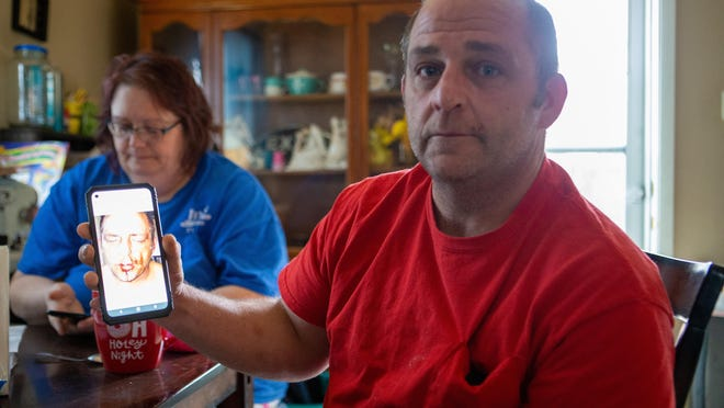 Michael Scott Dodson shows a photo taken Wednesday of his bloodied face as he sits Thursday at a table in his home with his wife, Jessica Risinger. Dodson talked Thursday with The Capital-Journal about how he was injured after Topeka police mistook him Wednesday for a man named Michael Eugene Dodson.