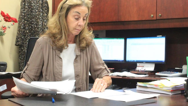 Sebastian County Circuit Clerk Denora Coomer looks through court records on Tuesday, Dec. 1, 2020, inside her office at the county courts building. Coomer is retiring after 37 years in the Sebastian County legal system.