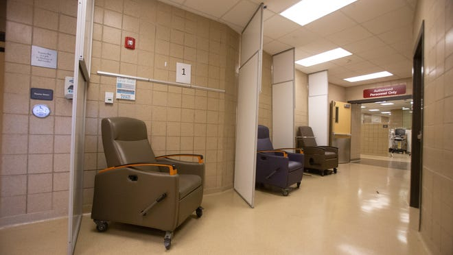Partitions divide single chairs set up to deal with overflow patients outside the trauma room at Stormont Vail Hospital.