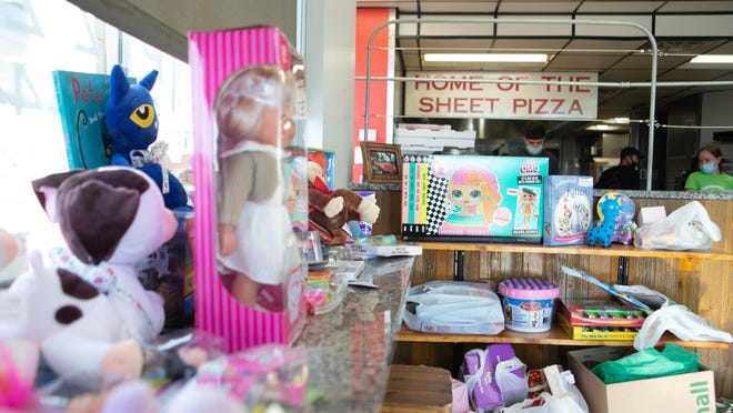 Toys fill the front of Topeka Pizza, 1630 S.W. Arvonia Place, Thursday afternoon. For the third consecutive year, the restaurant will offer customers who bring in at least two toys for donation to the Topeka Rescue Mission a free one-topping personal pizza.