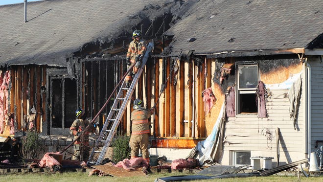 Firefighters work Wednesday evening at the scene of a house fire at 5144 Sand Creek Highway. The fire caused significant damage to the home. One person was taken to the hospital for burns but no other injuries were reported.