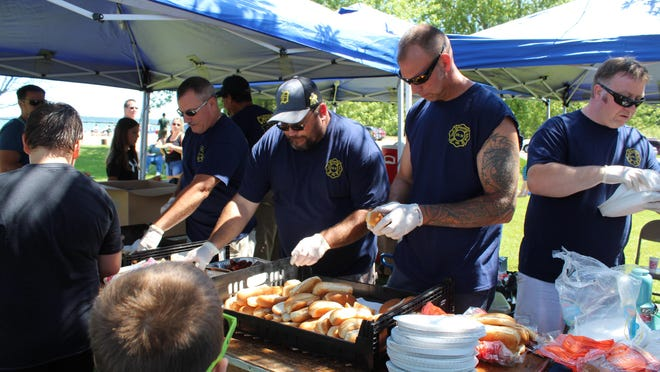Over 600 hot dogs are passed out each year by members of the Cheboygan Fire Department at their annual Kids Picnic at Gordon Turner Park. This year's event has been canceled. Tribune File Photo by Kortny Hahn