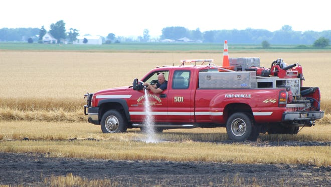 A firefighter from Metamora-Amboy Volunteer Fire Department in Ohio sprays down hot spots in a wheat field at the corner of Mulberry Road and Neuroth Highway on Monday. The field caught fire while farmers were harvesting wheat.