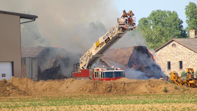 Firefighters use the Morenci Fire Department's aerial tower to direct water onto a barn fire Wednesday on West Weston Road.
