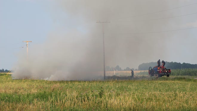 A crew of firefighters from Madison Township Fire Department work a field fire Monday along Weston Road in Ogden Township. The fire was caused by a downed power line but was extinguished quickly.
