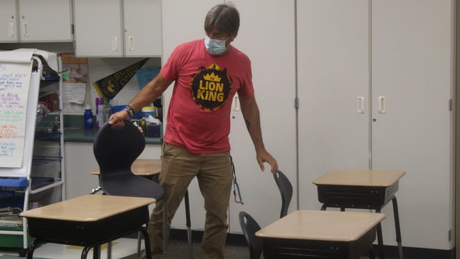 Prairie Elementary School Principal Carl Lewandowski helps set up a classroom Wednesday. Adrian Public Schools are preparing for a school year that will require a number of safety protocols and precautions due to COVID-19.